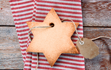 'yule tide': Traditional crispy star shaped Christmas cookie with attached blank tag on a rustic red and white striped napkin, overhead view
