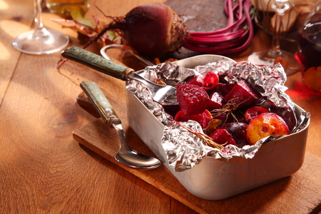 ambiente: Healthy roasted autumn beetroot diced with onions and cooked in the oven or BBQ in aluminum foil, high angle view in a metal roasting pan on a wooden table with copyspace