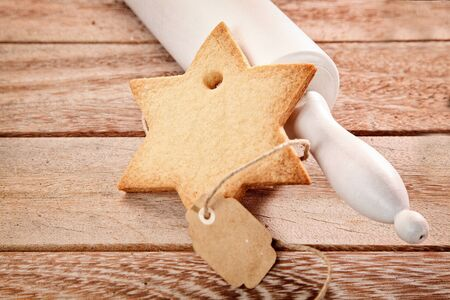 christmas tide: Traditional Christmas seasonal baking of golden crisp star shaped cookies with a rolling pin and freshly baked biscuit on a wooden counter