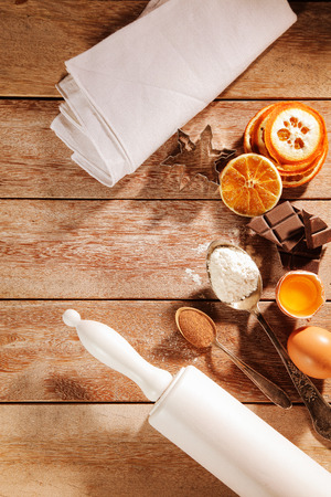christmas cooking: Overhead view of assorted traditional Christmas spices and baking ingredients with chocolate and orange slices alongside a wooden rolling pin on a wooden kitchen table Stock Photo