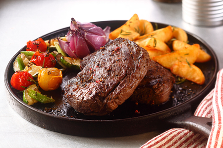 delicious: Close up Gourmet Appetizing Roasted Beef Steak with Potato Wedges and Other Vegetables on a Cast Iron Skillet.