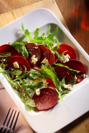 betabel: Plato de ensalada de remolacha fría con rúcula hojas frescas para una comida estacional de otoño, vista de ángulo alto