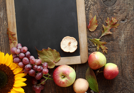 ambiente: Fresh autumn fruit and sunflower arranged around a blank vintage slate with copyspace for your menu or recipe with grapes, apples and mushroom on a rustic wooden counter
