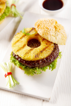 top angle: High Angle View of a Gourmet Tasty Hawaiian Burger with Pineapple Slice, Patty and Lettuce on a White Rectangular Plate.