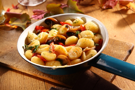 ambiente: Autumn mushrooms served with Italian gnocchi, or traditional semolina dumplings, seasoned with herbs and tomato in an old blue frying pan on a rustic wooden restaurant table Stock Photo