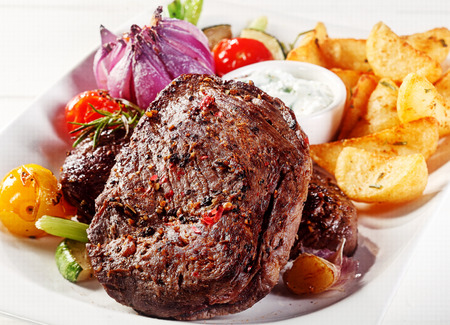 steak plate: Close up Gourmet Appetizing Pepper Crusted Beef Steak with Potato Wedges and Dipping Sauce on White Plate
