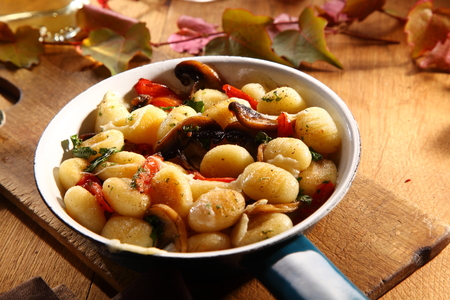 recipes: Tasty autumn recipe with gnocchi and mushrooms cooked with tomato and herbs and served in a frying pan at an Italian restaurant Stock Photo