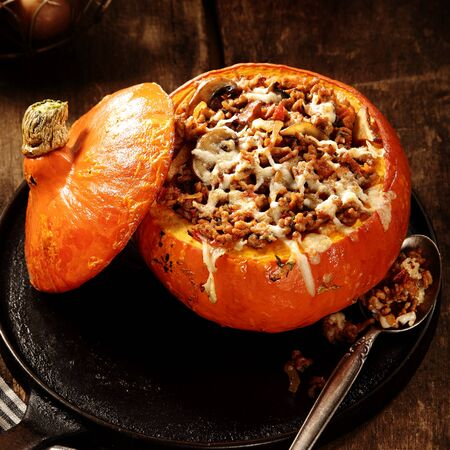 recipes: Delicious autumn recipe for stuffed pumpkin with fresh mushrooms mince meat and melted cheese ready to be served, high angle view of seasonal cuisine