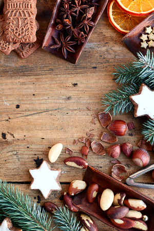 assorted: Festive border of nuts, cookies and spices with speculoos, star cookies, star anise, dried orange and assorted fresh nuts forming a border on a rustic wood background with copyspace