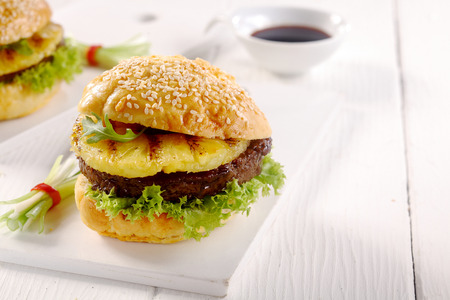 Close up Appetizing Hawaiian Burger with Patty, Pineapple and Lettuce on a White Table, Served on a White Table. Stock Photo