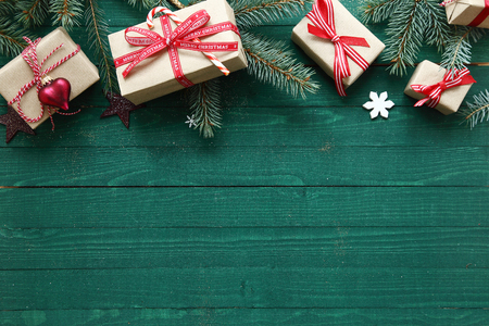 Christmas background with copyspace over rustic green wooden boards with a top border of decorative gifts and pine branches