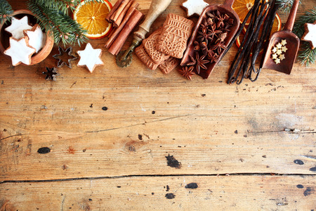 Traditional Christmas spices and cookies arranged as a top border over rustic wood background with cinnamon, star anise, speculoos and star biscuits and dried orange slices, large copyspace