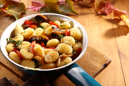 ambiente: Speciality Italian gnocchi with fresh autumn mushrooms flavored with tomato and served in a rustic blue frying pan on a wooden table Stock Photo
