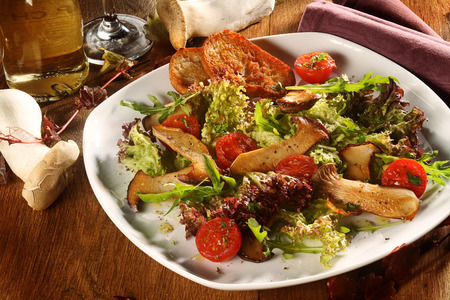 ambiente: Delicious autumn King Oyster mushroom salad with grilled mushrooms, tomato, fresh lettuce and rocket served in a bowl with toasted baguette