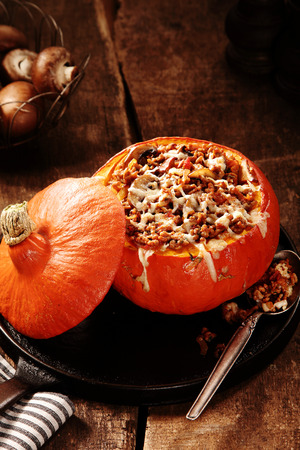 stuffing: Stuffed autumn squash or pumpkin with a savory stuffing of ground beef, mushrooms and melted cheese served with a spoon on a rustic wooden kitchen table Stock Photo