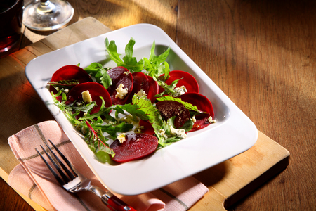 ambiente: Fresh beetroot salad with sliced cold beet and rocket served as a side dish to an autumn meal Stock Photo