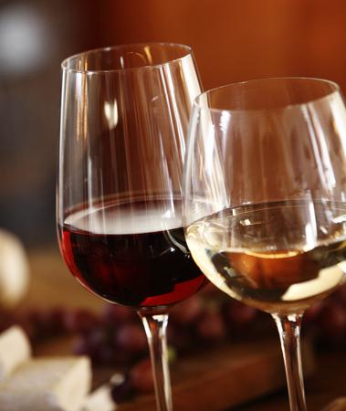 vasos: Gafas elegantes de vino tinto y blanco sirvieron juntos en una mesa de comedor para una comida formal, cerca de las copas de las copas y el vino
