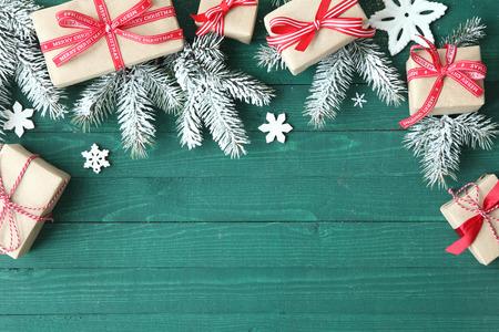Decoratieve Kerst achtergrond met geschenken gebonden met rood lint onder verse dennentakken met verspreide sneeuwvlok ornamenten op een groene houten tafel met copyspace voor uw begroeting