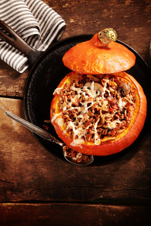Tasty autumn country dinner of stuffed pumpkin with a savory stuffing of ground beef, mushrooms and melted cheese, overhead view with the lid of the pumpkin put aside Stock Photo