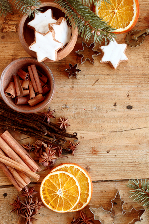 yule tide: Christmas spices and cookies in a festive frame with star cookies, cinnamon, star anise and dried orange slices over a rustic wooden background with copyspace, overhead view Stock Photo
