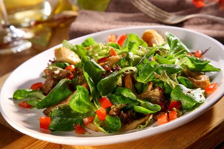 Tasty autumn salad with fresh King Oyster mushrooms, Pleurotus eryngii, in a bed of basil, herbs and tomato served in a bowl on a dinner table
