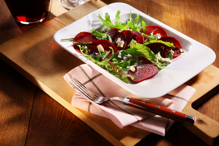 beetroot: Tasty autumn appetizer of fresh boiled beetroot salad with rocket served in a rectangular dish on a wooden board Stock Photo