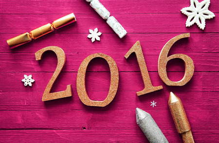 hogmanay: Simple 2016 New Year Celebration Design on a Wooden Magenta Table with Firecrackers and Snowflakes. Stock Photo