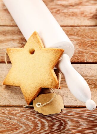 yule tide: Christmas seasonal baking concept with a delicious crisp fresh star shaped cookie and rolling pin on a wooden table, high angle view Stock Photo