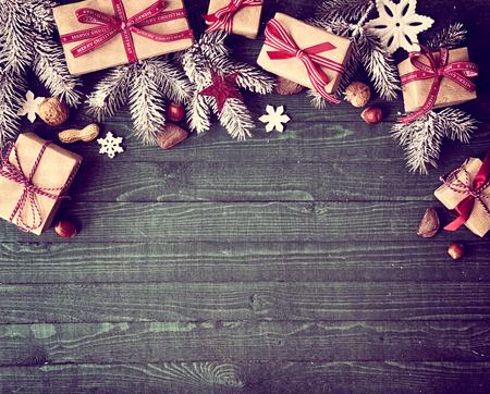 Seizoensgebonden rustieke grens Kerstmis bestaat uit decoratieve geschenken, dennentakken, noten en sneeuwvlok ornamenten over een houten achtergrond met copyspace, bovenaanzicht Stockfoto
