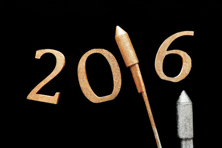 hogmanay: Simple 3D New Year 2016 Design with Gold and Silver Rocket Firecrackers Against Black Background.