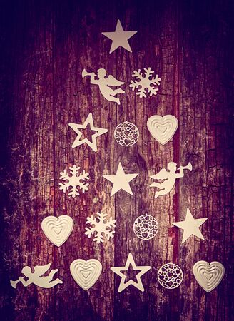 christmas stars: Decorative Christmas tree background on wood with an artistic arrangement of cutouts of angels, baubles, stars and snowflakes in a pyramid shape conceptual of an Xmas tree