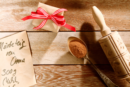rustic kitchen: Christmas baking concept with a gift-wrapped box, wooden rolling pin and spice in a teaspoon with a partial view of a handwritten recipe on a rustic wooden kitchen counter Stock Photo