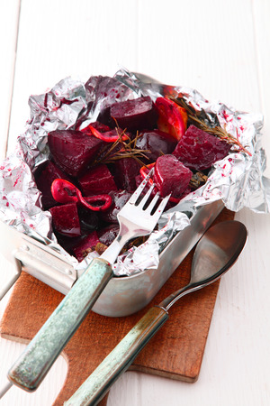 beetroot: Delicious oven roasted diced fresh beetroot with onions served in the baking dish in aluminum foil with rustic utensils - conceptual of seasonal autumn cuisine