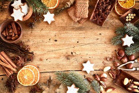 galletas de navidad: Marco tradicional de Navidad con especias, galletas, galletas speculoos estrellas y variedad de frutos secos decorados con naranja seca alrededor copyspace central sobre un fondo de madera rústica para su mensaje de Navidad Foto de archivo