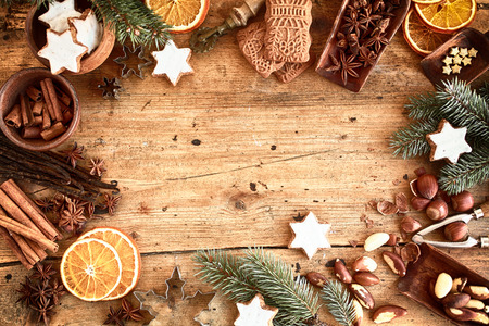 Traditional Xmas frame with spices, speculoos biscuits, star cookies and assorted nuts decorated with dried orange around central copyspace on a rustic wood background for your Christmas message Standard-Bild