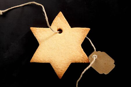 christmas tide: Golden fresh baked star cookie for Xmas tied with a blank tag over a black background with copyspace for your seasonal Christmas greeting Stock Photo