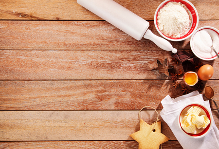 Baking ingredients with butter, flour and sugar with spices and orange in a Christmas border on a wooden background with copyspace viewed top down
