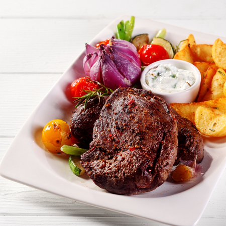 a portion: Close up Gourmet Tasty Roasted Beef Steak with Potato Slices, Dipping Sauce, Onion and Tomatoes on White Plate. Stock Photo