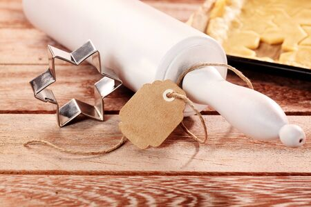yule tide: Baking traditional Christmas star cookies with a wooden rolling pin and old cookie cutter laid out beside rolled pastry on a wooden kitchen counter or table