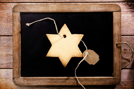 'yule tide': Freshly baked crispy golden star shaped Christmas cookie with a blank tag lying on a vintage school slate, overhead view