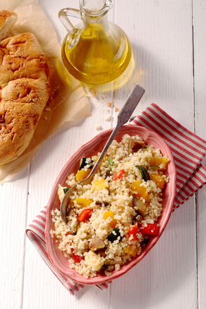 aerial view: Quinoa meal with bread with zucchini, peppers on white wooden table background