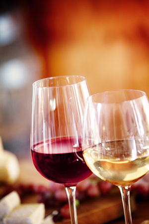 Glasses of red and chilled white wine on a dining table with background blur copyspace, close up view of the beverage