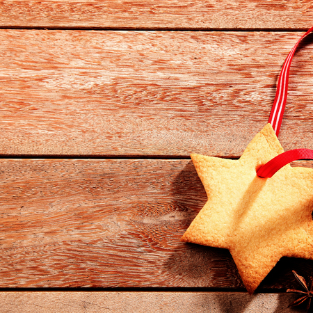 'yule tide': Delicious crispy Christmas cookie in the shape of a star with a red ribbon lying on a rustic wooden kitchen counter with copyspace for your greeting