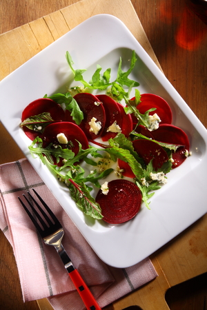 accompaniment: Cold beetroot and rocket salad served as an accompaniment to a fall or autumn dinner in a concept of seasonal cuisine, overhead view Stock Photo