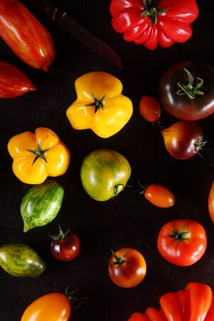 assortment: Colorful assorted fresh ripe organic tomatoes on a dark background for a healthy diet in a full frame view for agricultural or food themed concepts Stock Photo
