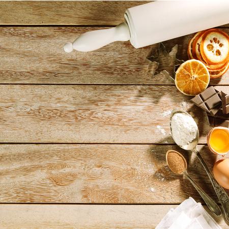 �pices: No�l cuisson fronti�re avec un assortiment d'�pices, de chocolat et d'orange s�ch�e affich� avec une cheville de bois de roulement sur table en bois avec copyspace, carr�e vue de format d'en haut