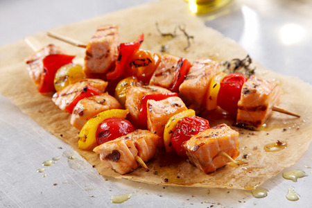 Three Flavored Fish Kebabs Brushed with Olive Oil on a Paper on Top of a White Table. Stok Fotoğraf