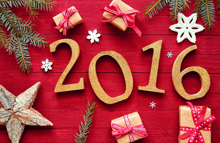 Gold 2016 for New Year And Christmas Design on Red Wooden Table with Fir Leaves, Snowflakes, Gift Boxes and Star
