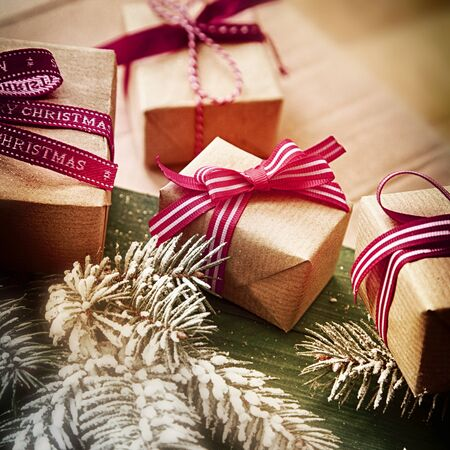 yule tide: Christmas gift background with four gift-wrapped presents tied with red ribbon and bows with fresh pine foliage on a wooden background, close up view in square format