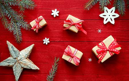 Barevné červené vánoční pozadí s čerstvými větví borovice, hvězdy, vločky a dekorační dary svázané s pásem karet a luky rozptýlené na slavnostní červeném pozadí, režijní zobrazení
